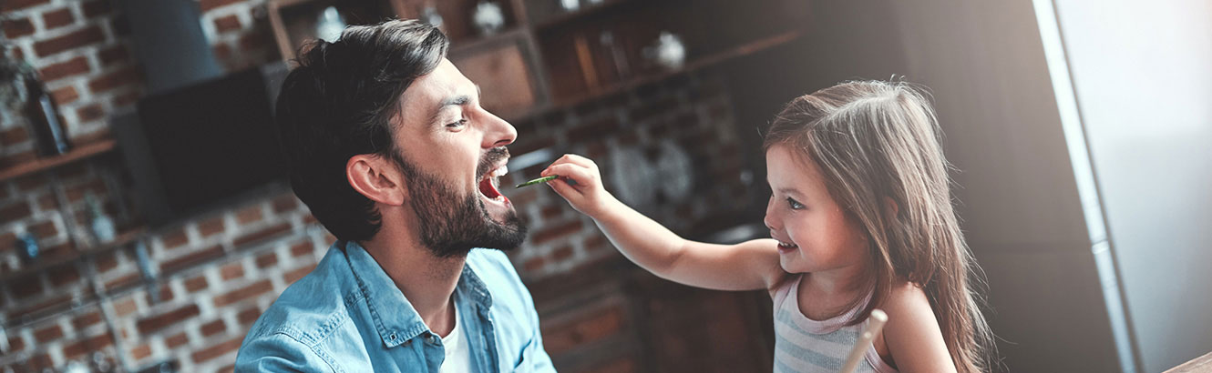 Father and daughter eating in kitchen